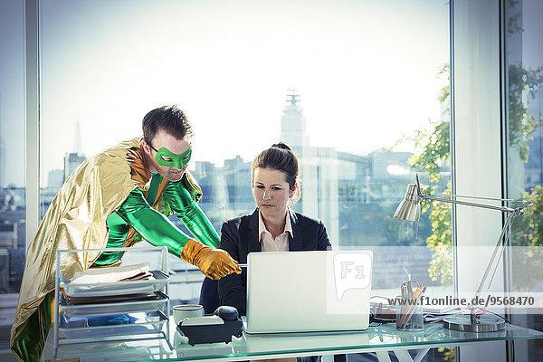 Superheldin hilft Geschäftsfrau bei der Arbeit am Schreibtisch