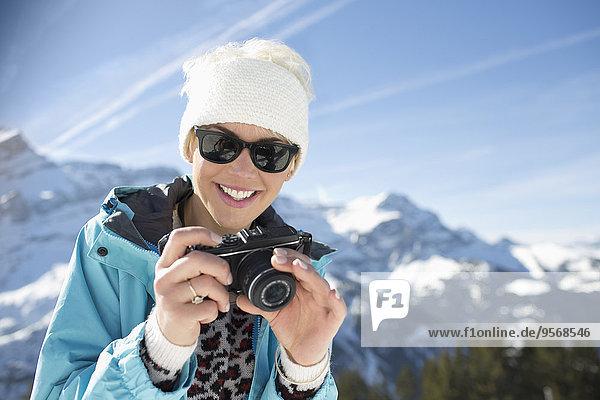 Porträt einer lächelnden Frau mit Kamera in den Bergen