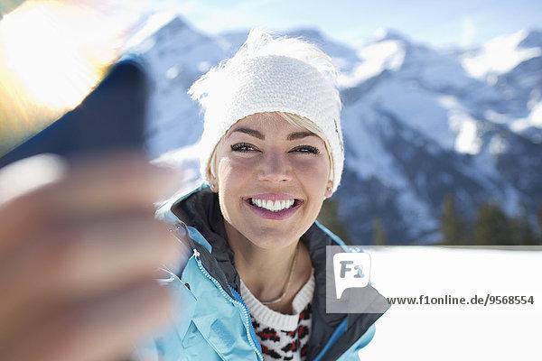 Smiling woman taking selfie in snow
