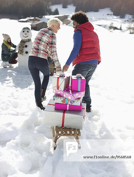 Paar Ziehschlitten mit Weihnachtsgeschenken im Schnee