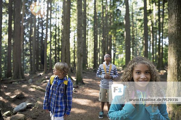 Jungen und Mädchen mit Rucksäcken im Wald