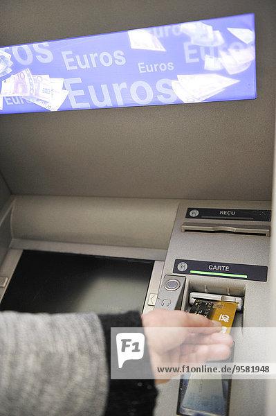 Junge Frau zieht Geld von einem Geldautomaten ab