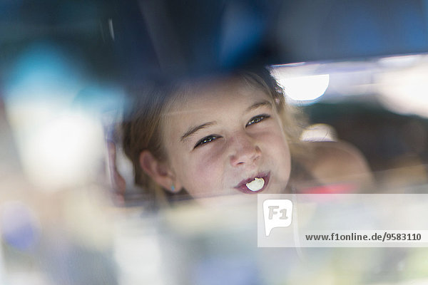 Reflection of Caucasian girl blowing bubble gum bubble in rearview mirror