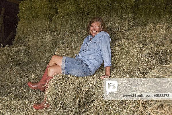 Older Caucasian woman sitting on hay bales