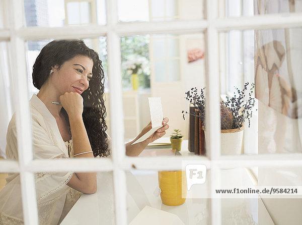 Mixed race woman reading card near window