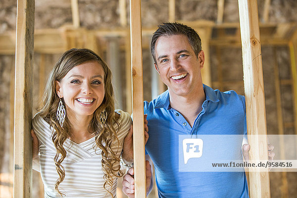 Caucasian couple smiling in house under construction