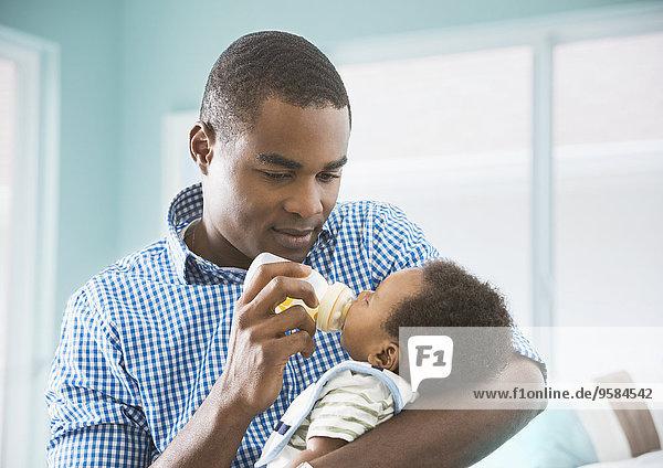 Father bottle feeding baby son