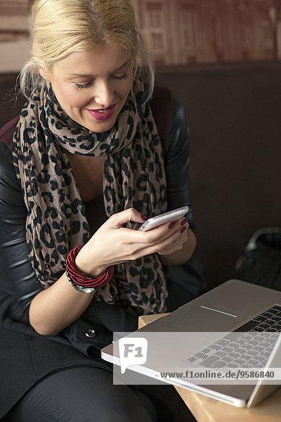 Handy benutzen Frau Notebook Cafe
