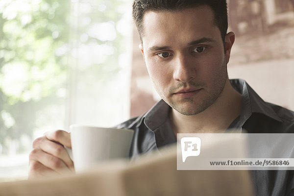 Mann Tasse trinken Kaffee Zeitung vorlesen
