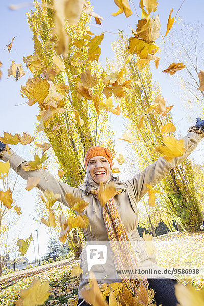 Older Caucasian woman playing in autumn leaves