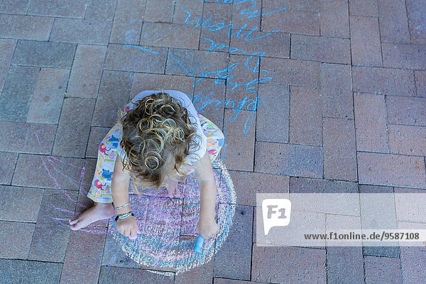 Caucasian boy drawing with chalk on patio