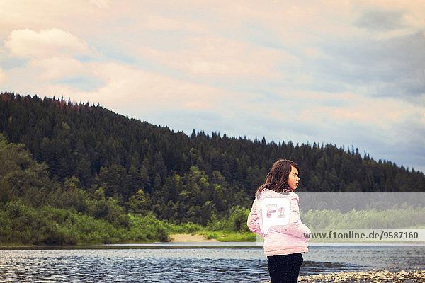 Caucasian girl standing at remote lake