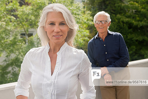 Portrait of mature woman standing on balcony with her husband in background