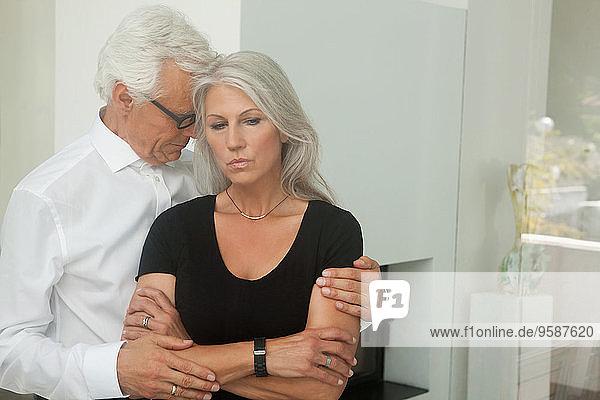 Ehemann  der seine traurige Frau tröstet.