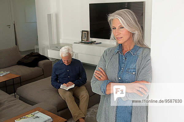 Porträt einer älteren Frau  die sich an eine Wand lehnt  während ihr Mann im Hintergrund ein Buch liest.