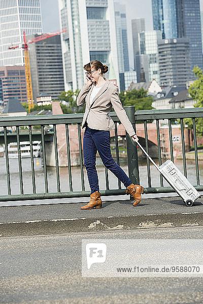 Deutschland  Hessen  Frankfurt  telefonierende Geschäftsfrau mit rollenden Koffern über eine Brücke gehend