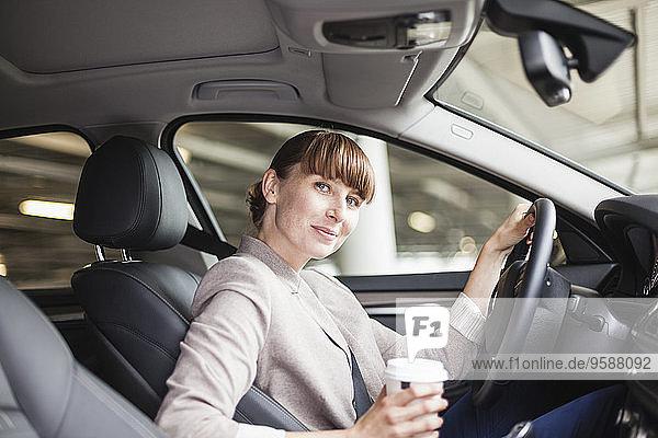Deutschland  Hessen  Frankfurt  Porträt einer lächelnden Geschäftsfrau mit Kaffee zum Mitnehmen im Auto