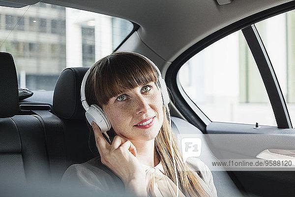 Porträt einer lächelnden Geschäftsfrau mit Kopfhörer  die im Auto Musik hört.