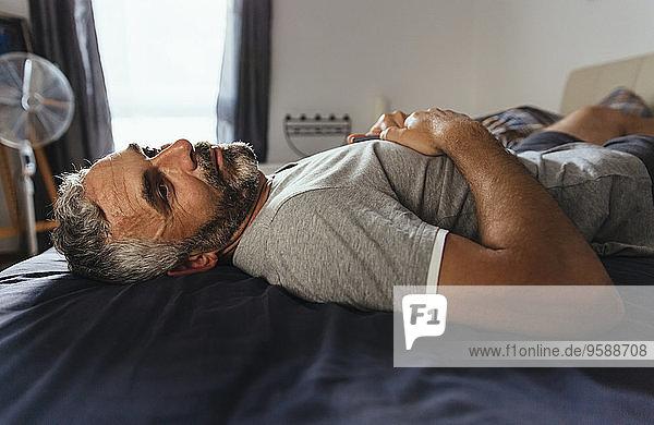 Nachdenklicher Mann  der tagsüber auf seinem Bett liegt.