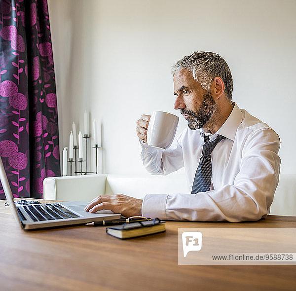 Porträt eines Geschäftsmannes  der zu Hause arbeitet und Kaffee trinkt.