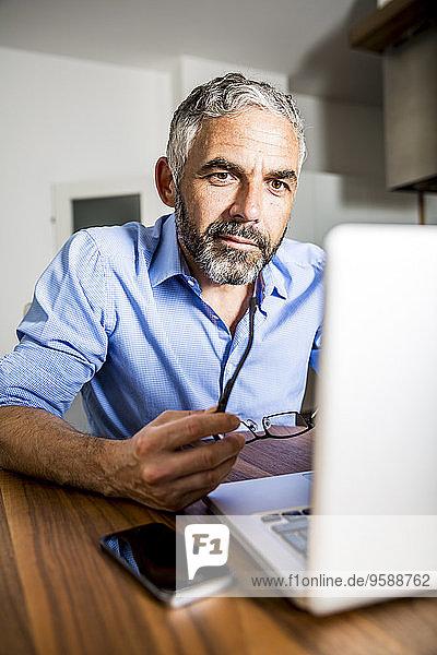 Portrait eines Geschäftsmannes  der mit dem Laptop im Home-Office arbeitet
