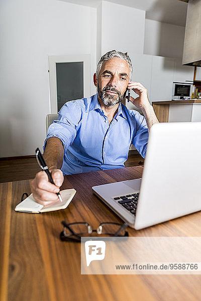Portrait eines Geschäftsmannes  der mit seinem Smartphone telefoniert und dabei Notizen macht.
