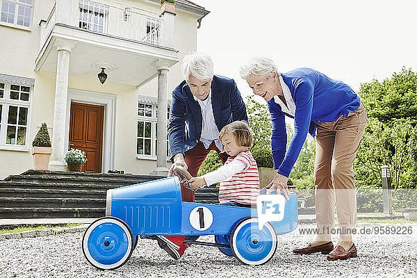 Deutschland  Hessen  Frankfurt  Seniorenpaar mit Enkelin sitzend Tretauto