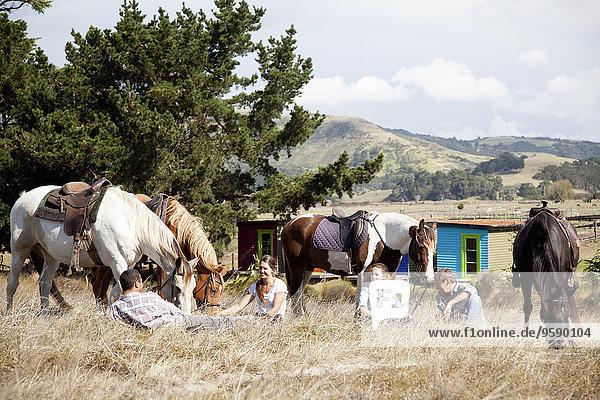 Reiter machen Pause auf Rasen  Pakiri Beach  Auckland  Neuseeland