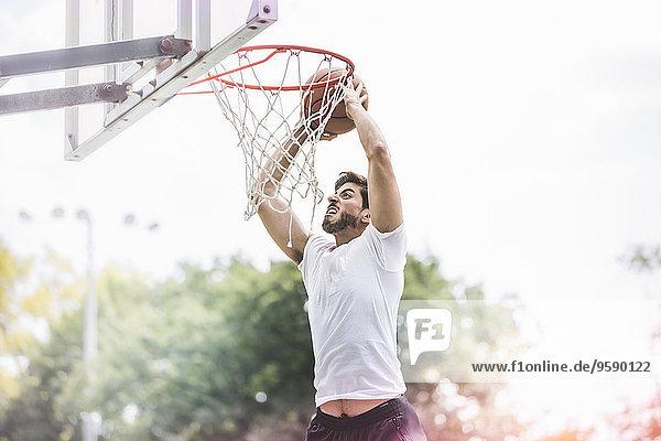 Junger Basketballspieler springt mit Ball  um zu punkten. Junger Basketballspieler springt mit Ball, um zu punkten.