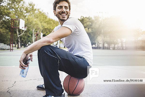 Porträt eines jungen Basketballspielers auf dem Ball sitzend