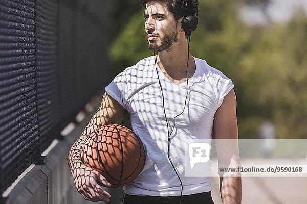 Junger Basketballspieler  der über die Fußgängerbrücke läuft und Kopfhörer hört. Junger Basketballspieler, der über die Fußgängerbrücke läuft und Kopfhörer hört.