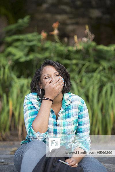 Junge Frau lacht mit handbedecktem Mund