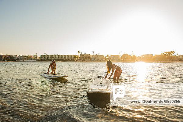 Zwei Frauen beim Paddeln bei Sonnenuntergang  Mission Bay  San Diego  Kalifornien  USA