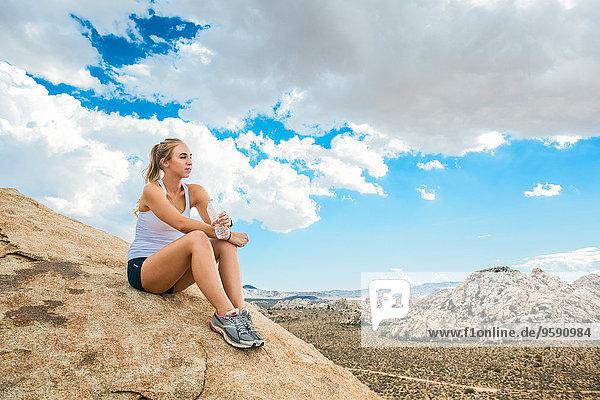 Frau macht Pause am Berg  Joshua Tree National Park  Kalifornien  USA