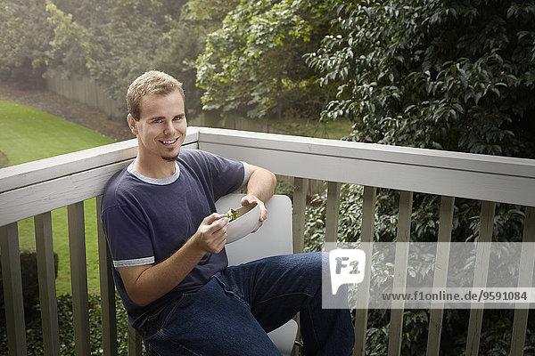 Young man having salad on balcony