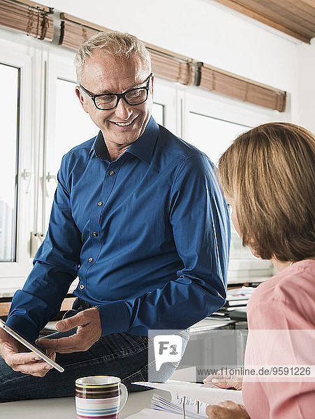 Smiling businessman and woman in office