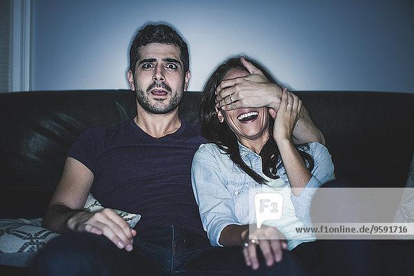 Paar beobachtet Thriller auf dem Sofa Paar beobachtet Thriller auf dem Sofa