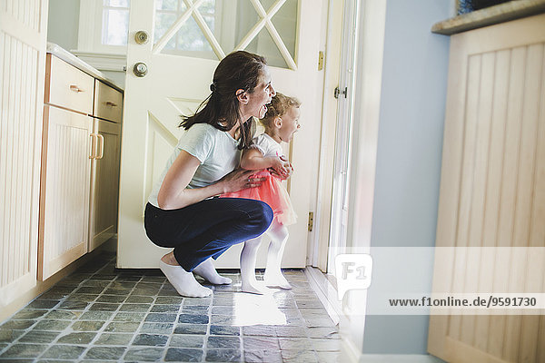 Mutter und Tochter lachen über die Tür.
