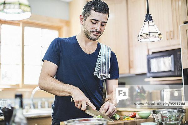 Mann bei der Zubereitung von Speisen in der Küche Mann bei der Zubereitung von Speisen in der Küche
