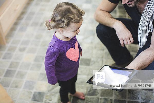 Vater und Tochter mit digitalem Tablett in der Küche Vater und Tochter mit digitalem Tablett in der Küche