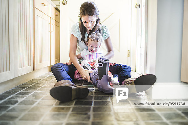 Mother and daughter putting on boots in kitchen
