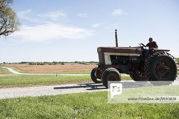 Bauer fährt Traktor auf Landstraße  Missouri  USA