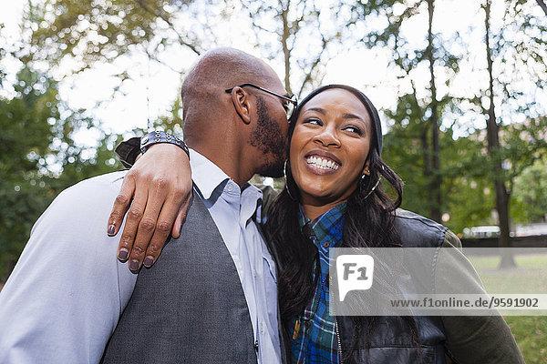 Mann küsst Wange der Frau im Park