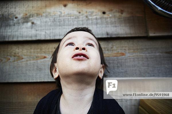 Portrait des männlichen Kleinkindes vor dem Schuppen mit Blick nach oben