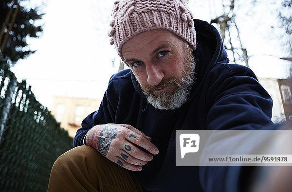 Erwachsener Mann hockt mit ausgestrecktem Arm  um sich selbst zu porträtieren.