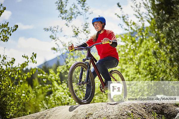 Junge Bikerin auf dem Felsrand im Wald