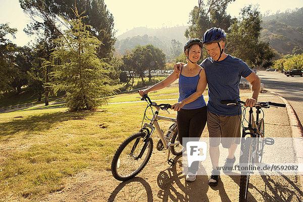 Reife Paare plaudern beim Fahrradfahren im Park