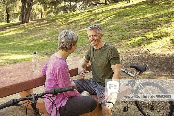 Ein reifes Radfahrerpaar macht eine Pause auf dem Picknicktisch im Park.
