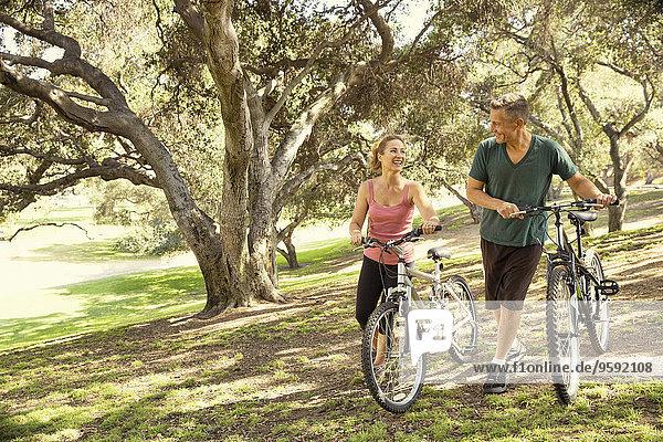 Reife Paare beim Plaudern und Schieben von Fahrrädern durch den Park