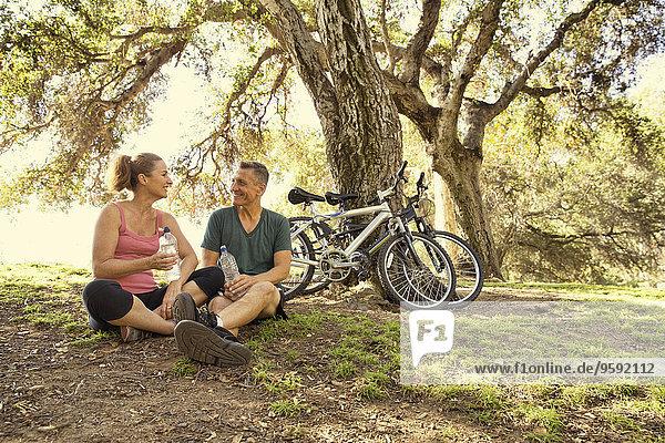 Ein reifes Radfahrerpaar bei einer Wasserpause im Park